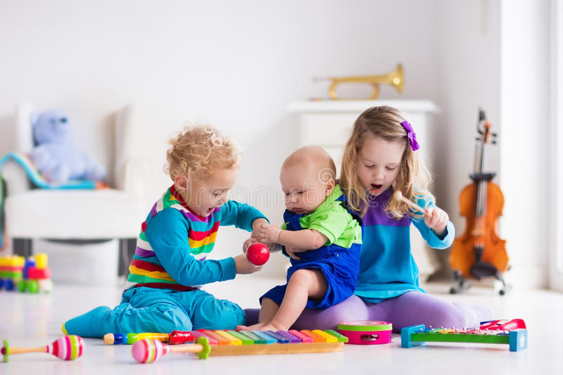 Music for kids, children with instruments. Children with music instruments. Musical education for kids. Colorful wooden art toys. Little girl and boy play music royalty free stock photo