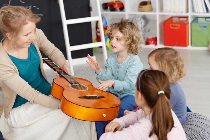 Music lesson with kids. Young teacher having music lesson with small kids in kindergarten royalty free stock photo