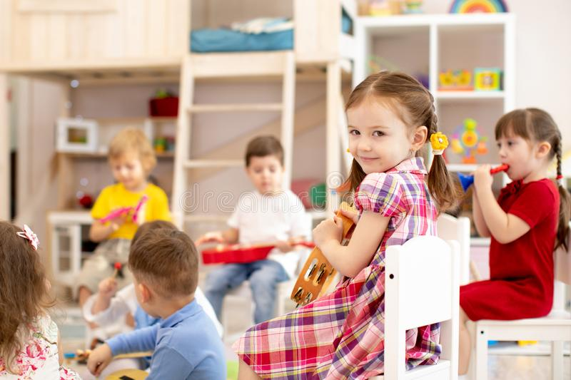 Music lesson in primary school. Kids group playing musical instruments royalty free stock images