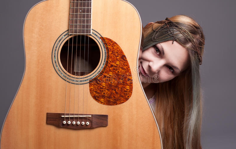 Music love. Young hippie lady loves her guitar and smiling