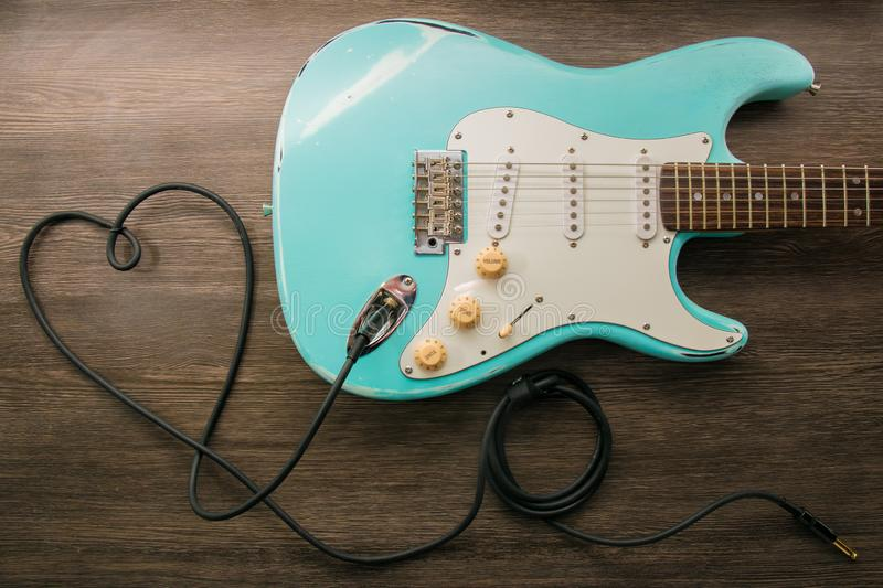 Music love concept. Wire jack heart guitar. Light blue electric guitar in a wood texture royalty free stock images