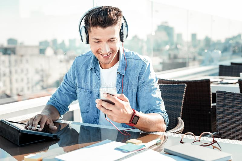 Concentrated brunette reading his message. Music lover. Cheerful male person bowing head and smiling while choosing necessary song stock photo