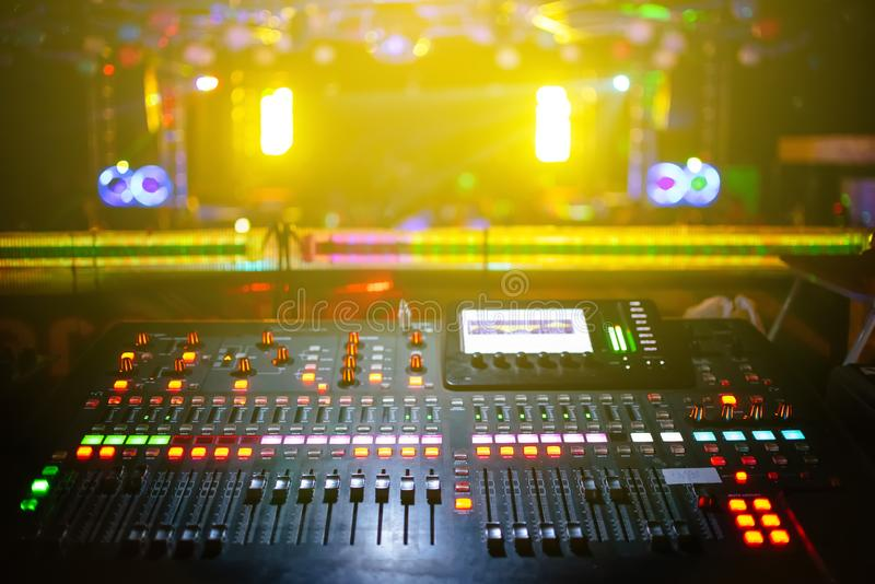 Music mixer with stage, concert background blurred, yellow light. In nightclub stock image