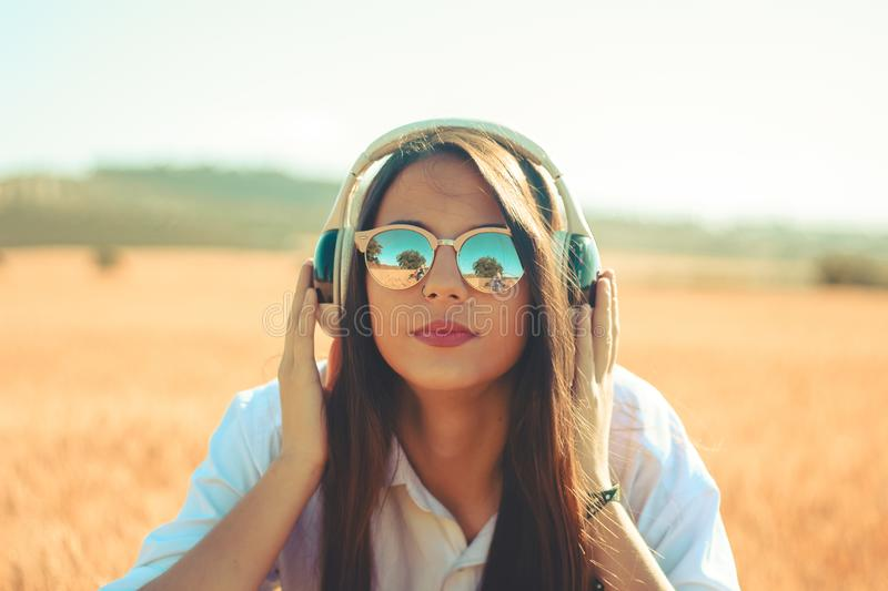 Music in my life. AA young girl using wireless headphones and wearing sunglasses outdoor royalty free stock images