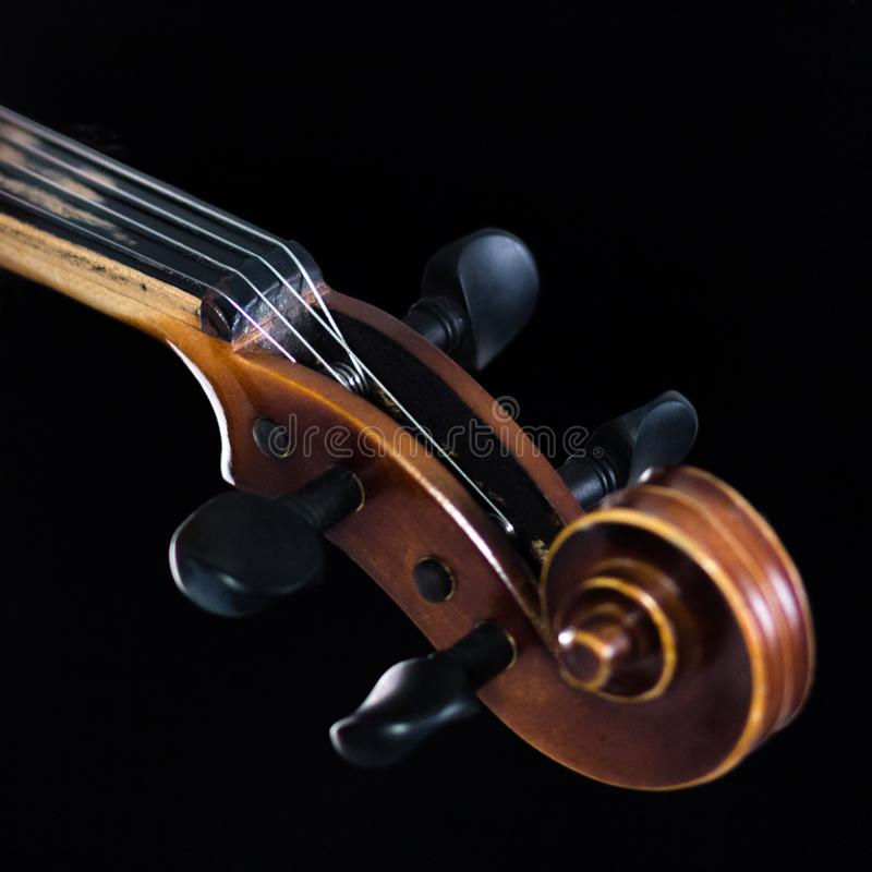 The extreme part of the violin fretboard is on a black background. A close-up of a tin box and a classic curl. For music news. A s royalty free stock photography