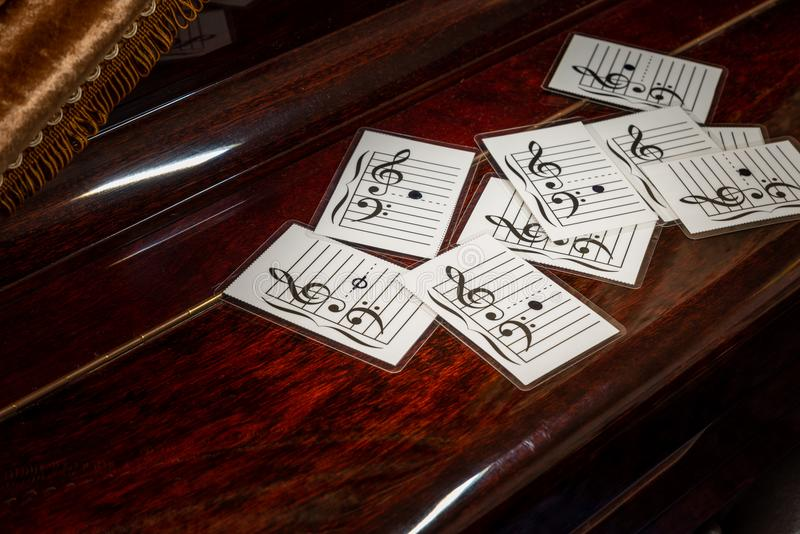 Music note on flash cards. On old wooden piano. Concept for learning music note with flash cards stock images