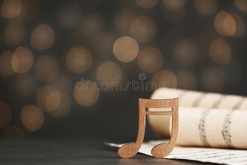 Music note and sheets on table against blurred lights. Bokeh effect. Music note and sheets on table against blurred lights, space for text. Bokeh effect stock photo