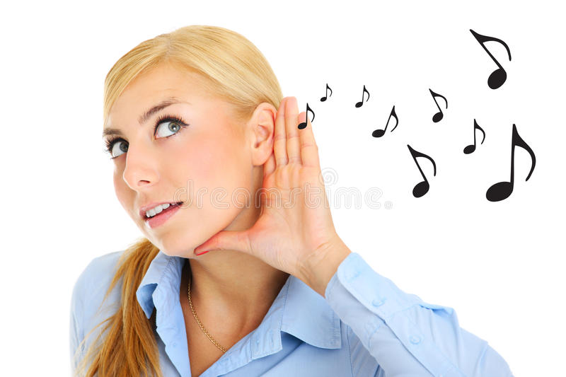Music notes. A picture of a young woman listening to music notes over white background royalty free stock photo