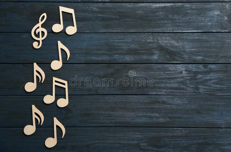 Music notes and treble clef on wooden background, top view. Space for text royalty free stock photos