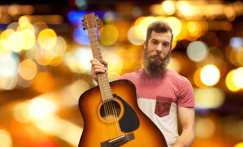 Male musician with guitar over night city lights. Music, people and musical instruments concept - male musician with acoustic guitar over night city lights stock photo