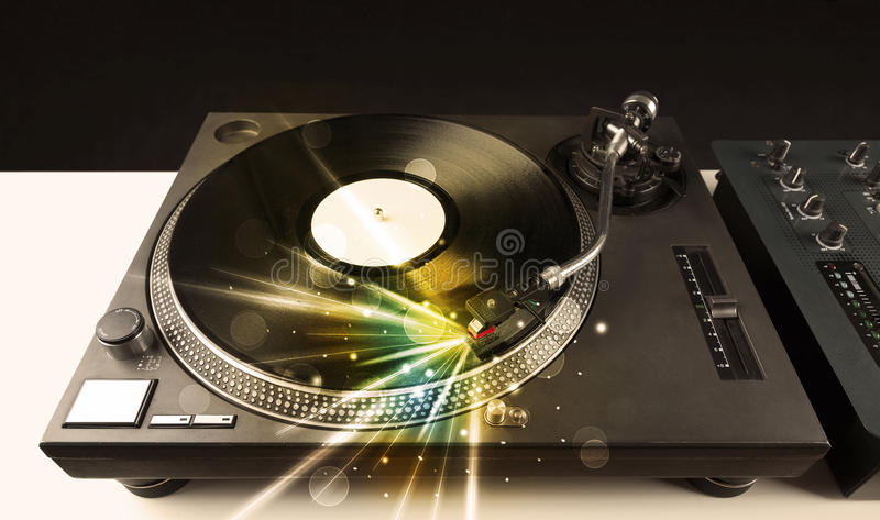 Music player playing vinyl with glow lines comming from the need stock photo