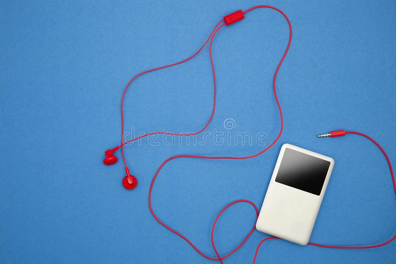 Music player with red earphone on blue paper background. Music player with red earphone on blue paper background stock images