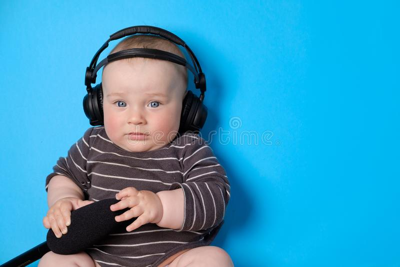 Music or podcast background with baby boy with headphones and microphone on blue table, flat lay. Top view, flat lay stock photography