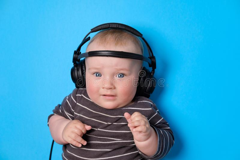 Music or podcast background with baby boy with headphones and microphone on blue table, flat lay. Top view, flat lay royalty free stock photography