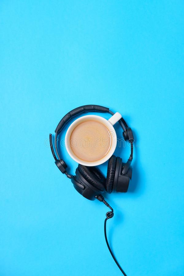 Music or podcast background with headphones and cup of coffee on blue table, flat lay. Top view, flat lay royalty free stock image