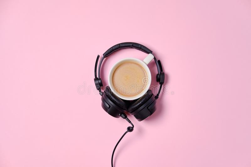Music or podcast background with headphones and cup of coffee on pink table, flat lay. Top view, flat lay stock photography
