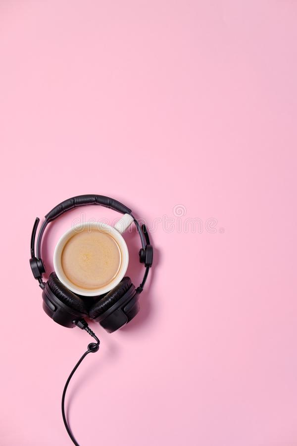 Music or podcast background with headphones and cup of coffee on pink table, flat lay. Top view, flat lay stock photos
