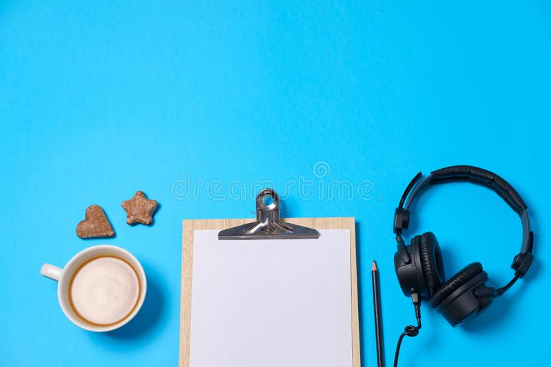 Music or podcast background with headphones, microphone, coffee and blank on blue table, flat lay. Top view, flat lay royalty free stock images