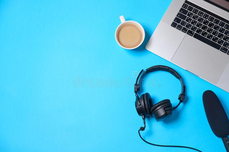 Music or podcast background with headphones, microphone, coffee and laptop on blue table, flat lay. Top view, flat lay royalty free stock images