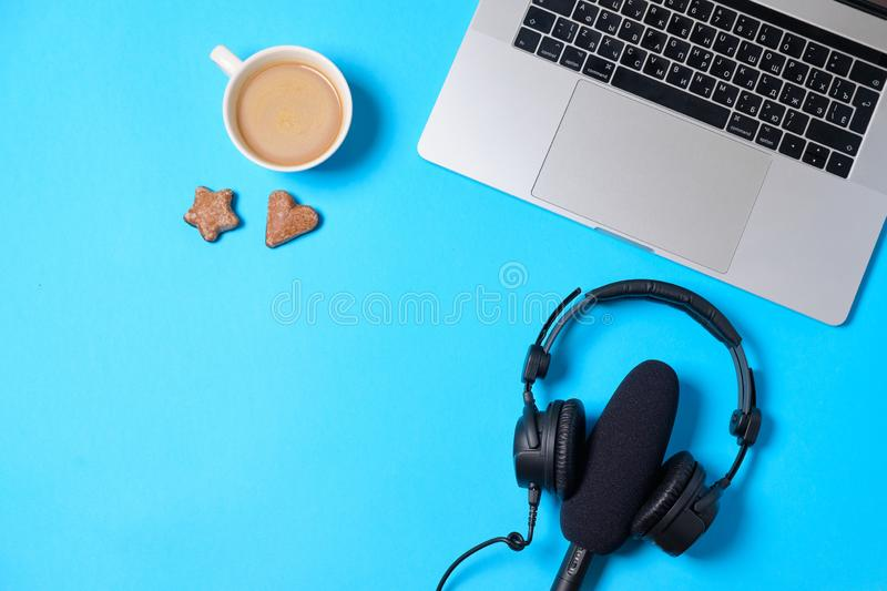 Music or podcast background with headphones, microphone, coffee and laptop on blue table, flat lay. Top view, flat lay stock images
