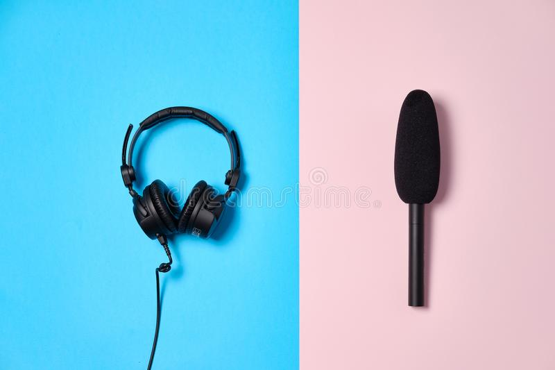 Music or podcast background with headphones and microphoneon blue table, flat lay. Top view, flat lay stock images