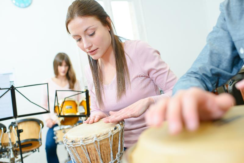 Music rehearsal woman playing bongos royalty free stock photography
