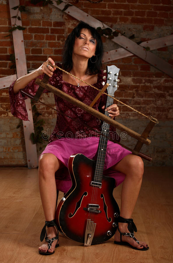 Music sadness. Sad woman with flowing make-up plays the guitar saw royalty free stock photo