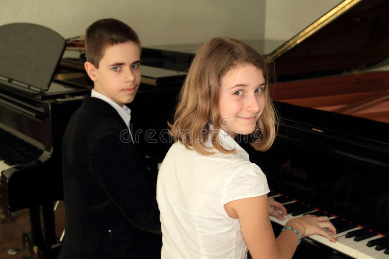 In the music school. In music school boy and a girl playing the piano for four hands stock photo
