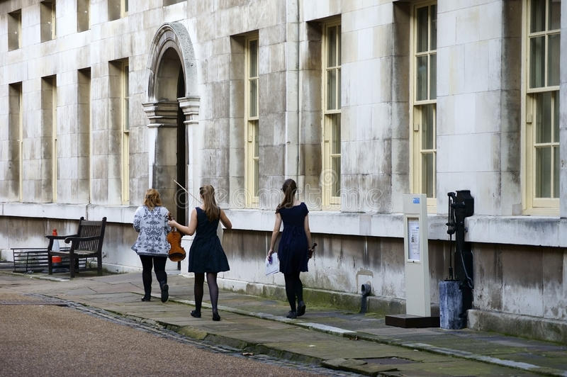 Music School in Royal Naval College. London, UK - November 29, 2014: A music teacher walks with her two students to violin lessons in an exercise room of the stock photography