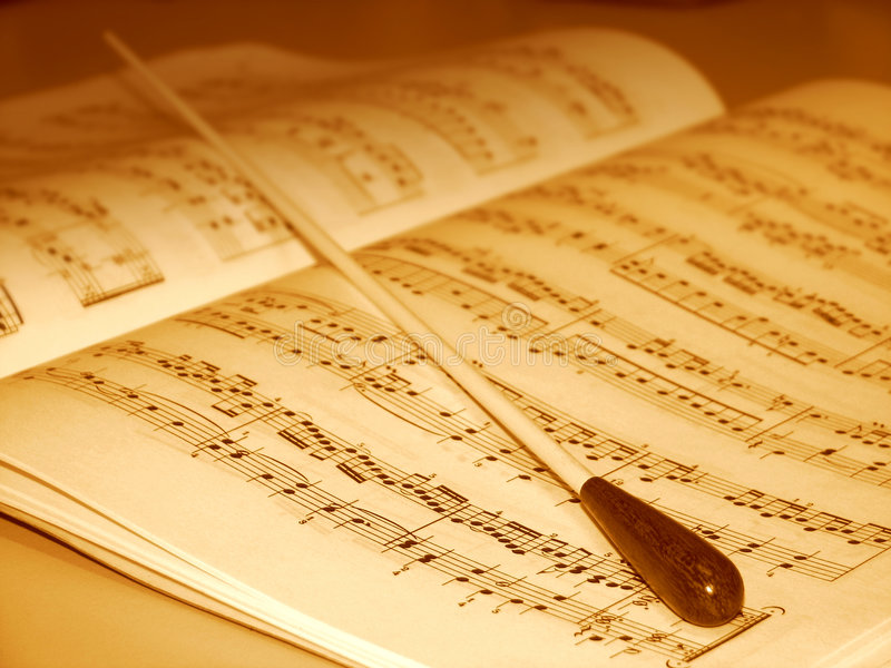Music score and conductor's baton. A conductor's baton laying across the music score stock photos