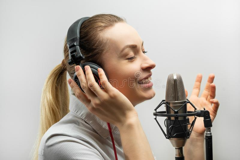 Music, show business, people and voice concept - singer with headphones and microphone singing a song in recording studio,. Recording news, blog, announcer stock photography