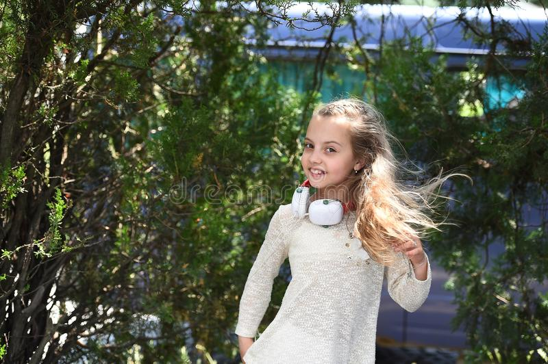 Music sound in mp3. Happy girl dance to music in summer park. Small child enjoy music in headphones outdoor. Kid dancer. Smile with long flying hair. Summer fun stock photos