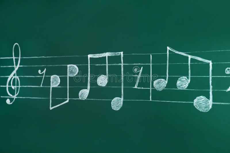 Music staff with treble clef and notes written. On chalkboard royalty free stock photo