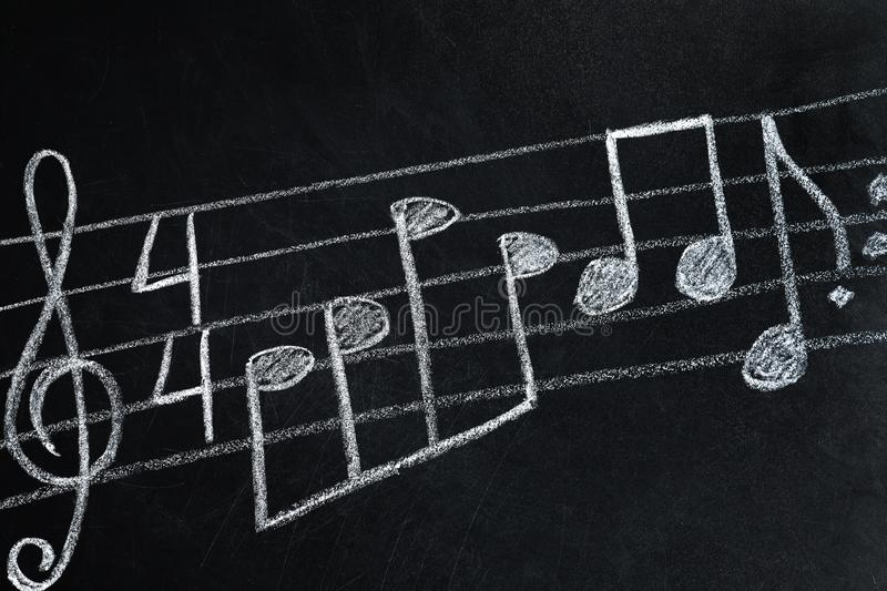 Music staff with treble clef and notes written. On chalkboard royalty free stock photos