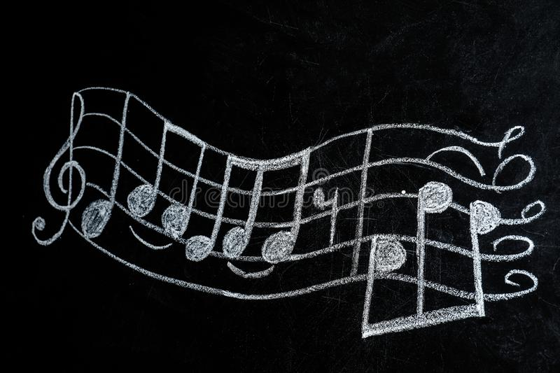 Music staff with treble clef and notes written. On chalkboard royalty free stock images