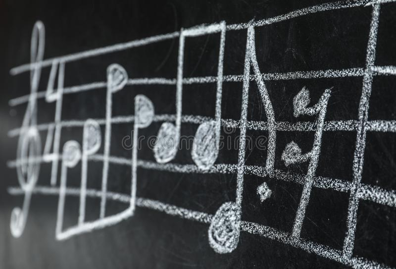 Music staff with treble clef and notes written. On chalkboard stock image