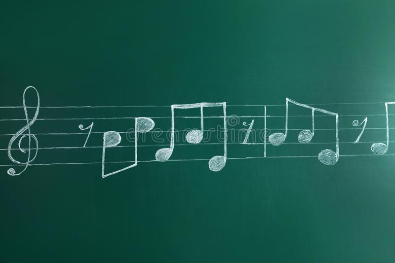 Music staff with treble clef and notes. Written on chalkboard stock image