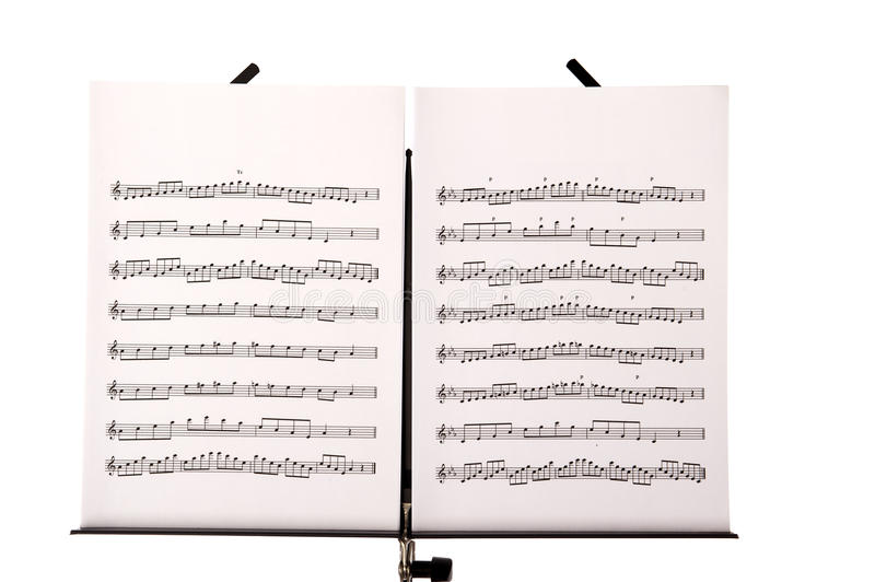 Music stand with melody sheets. Melody sheets on a music sheet stand isolated in white stock photo