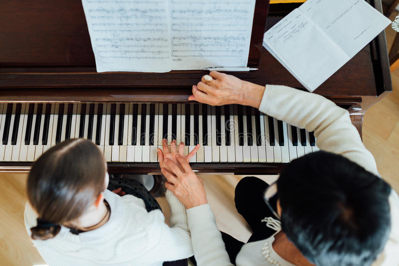 Music teacher with the pupil at lesson piano,. A music teacher with the pupil at the lesson piano, top view stock images