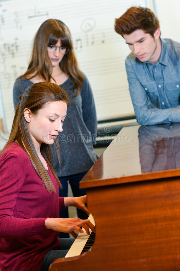 Music teacher with two pupils during piano lesson royalty free stock photography