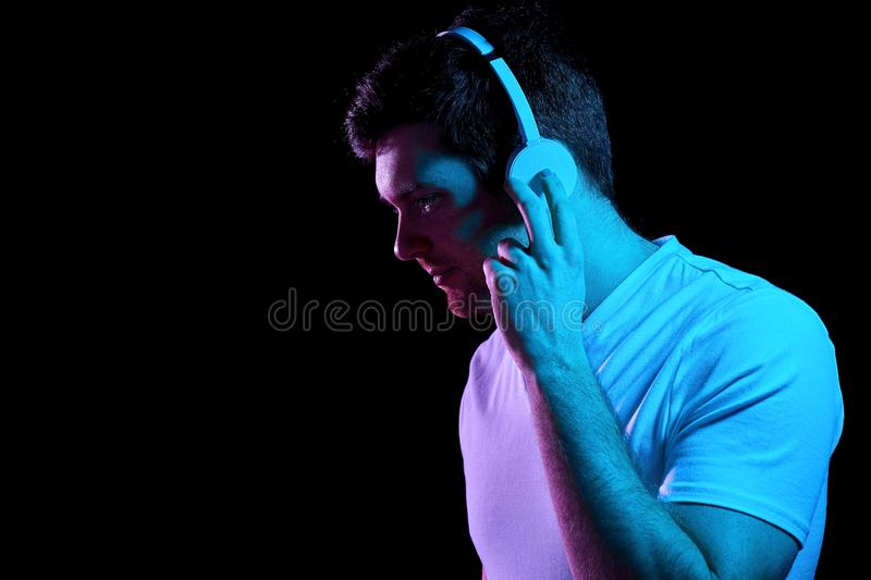 Man in headphones over neon lights of night club royalty free stock photography