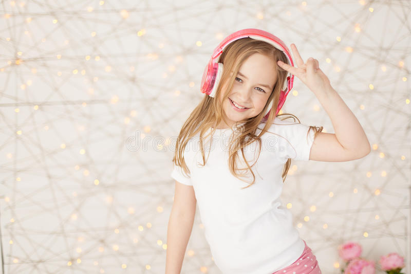 Music and technology. Young girl with pink wireless headphones make peace by hand on background with lights. Pastel royalty free stock photos