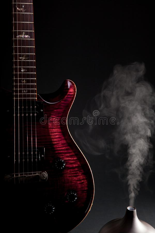 Music therapy. Electric guitar with aromatherapy oil diffuser de stock photos