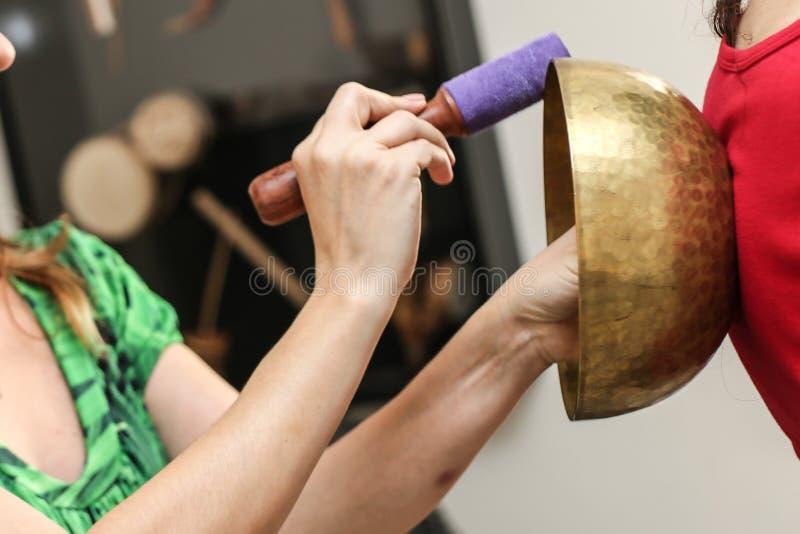 Music therapy Tibetan Bowls. A woman playing Music therapy Tibetan Bowls royalty free stock photos