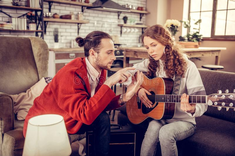 Music tutor teaching girl to move fingers while playing the guitar royalty free stock photos