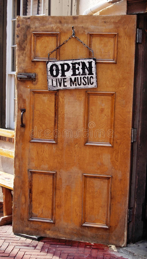 Music Venue. Open door to a local bar with a sign announcing OPEN LIVE MUSIC invites patrons in royalty free stock photos
