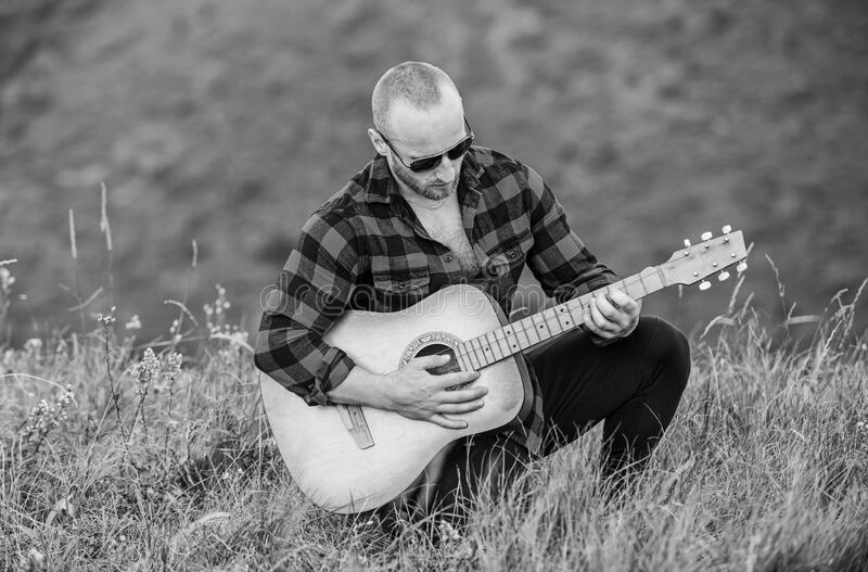 Music is what I am. country music song. sexy man with guitar in checkered shirt. hipster fashion. western camping and. Hiking. happy and free. cowboy man with stock photos
