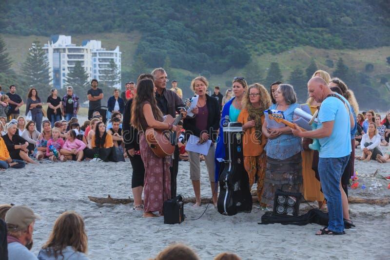 Musica ad una veglia della spiaggia per vittime della fucilazione della moschea di Christchurch, Nuova Zelanda immagine stock
