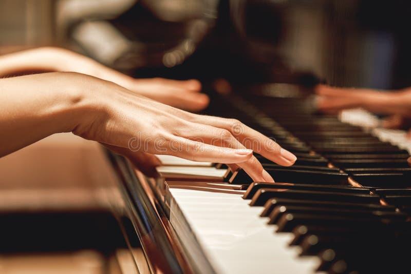 Musica classica favorita Vista alta vicina delle mani femminili delicate che giocano una melodia sul piano mentre prendendo le le fotografia stock