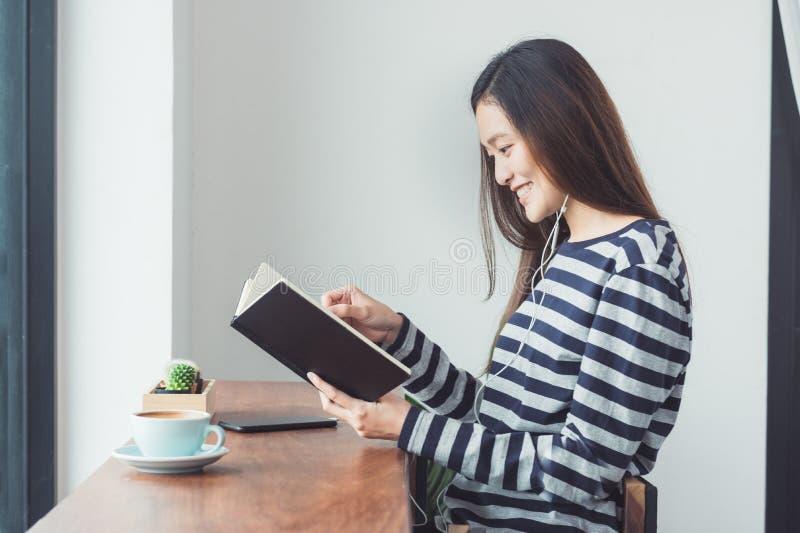Musica d'ascolto asiatica del libro di lettura della donna con il cellulare che si siede a fotografie stock libere da diritti